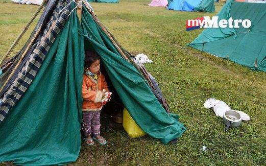 SEORANG budak berdiri di pintu khemah yang dikongsi bersama ahli keluarganya di Kathmandu.