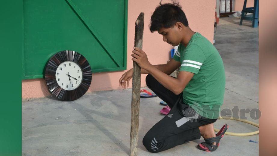 MUHAMMAD Aiman menentukan arah kiblat dengan menegakkan kayu antara jam 5.10 hingga 5.20 petang di kediamannya. FOTO Hassan Omar