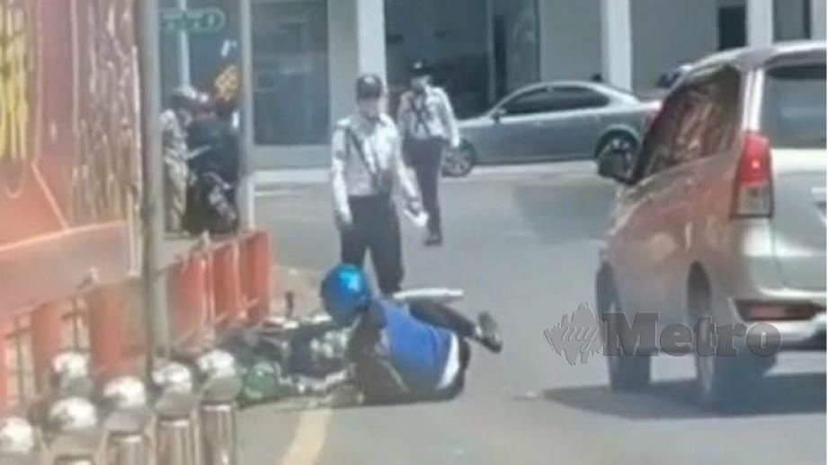 TANGKAP layar video tular yang menunjukkan seorang penunggang motosikal terjatuh selepas ditendang anggota trafik.