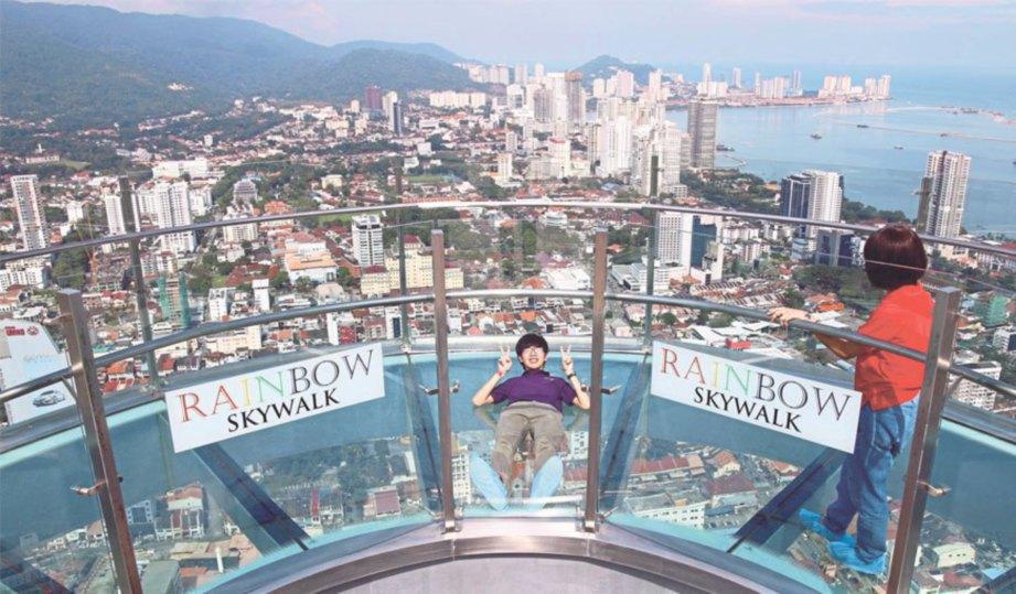 PENGUNJUNG berjalan di atas laluan gantung Rainbow Skywalk yang berlantaikan kaca pada ketinggian 244.6 meter.