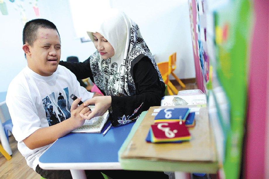 SEORANG guru, Siti Nurul Hidayah Amran memberikan tunjuk ajar kepada pelajar sindrom Down, Amirul Hakim Safa'ei di PKIB.
