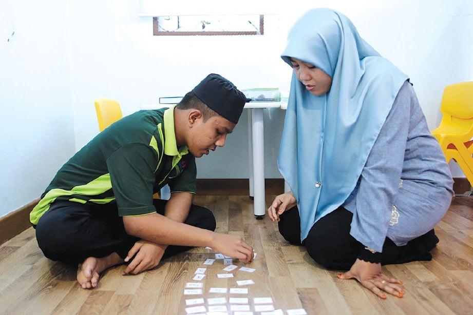 SABARIAH meluangkan masa melihat aktiviti anaknya, Muhammad Nor Aiman Norizan yang merupakan pelajar di di PKIB.