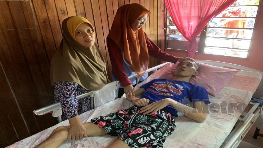 NORAZLIN dan Siti Rohani menguruskan Shamsul Hafiz yang terlantar akibat angin ahmar. FOTO Noor Hidayah Tanzizi.