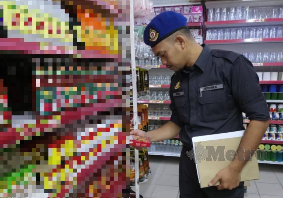 ANGGOTA penguat kuasa KPDNHEP Melaka melakukan pemeriksaan produk dalam operasi, kelmarin. FOTO Ihsan KPDNHEP Melaka.