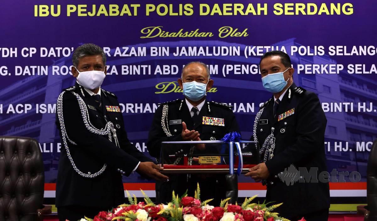ISMADI (kiri) menyerahkan tongkat kuasa kepada Razali (kanan) pada majlis Serah Terima Tugas Ketua Polis Daerah Serdang di IPD Serdang. FOTO Hairul Anuar Rahim