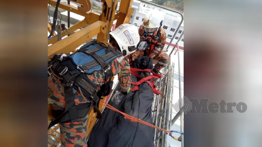 ANGGOTA bomba mengambil masa dua jam untuk menurunkan mayat pengendali kren pada ketinggian tingkat 12 bangunan di Danga Twin Resident, Johor Bahru, hari ini. FOTO ihsan bomba.