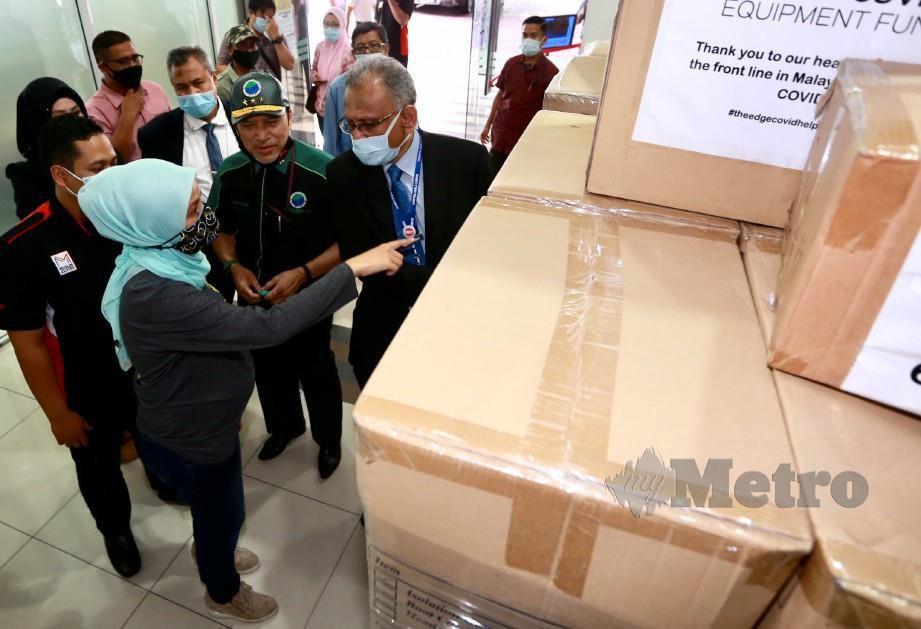SITI Khadijah (kiri) menunjukkan kelengkapan pakaian pelindungan diri (PPE ISOLATION) yang di sumbangkan kepada Dr Heric di Lobi Hospital Besar Kuala Lumpur. FOTO FATHIL ASRI.