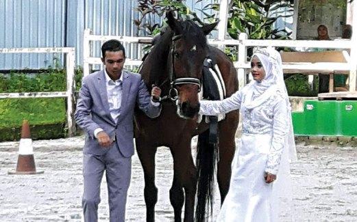 PASANGAN pengantin baru turut merakamkan detik bersejarah bersama kuda.