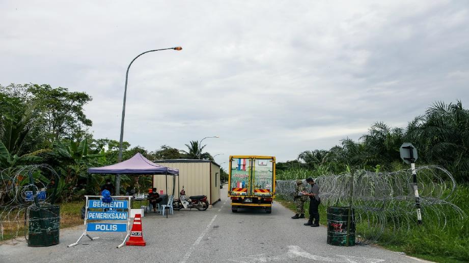 ANGGOTA Polis dan Angkatan Tentera Malaysia berkawal di pintu masuk dan keluar ke kawasan Pangsapuri Taman Langat Utama dan Pangsapuri Taman Langat Murni, Kuala Langat. FOTO LUQMAN HAKIM ZUBIR