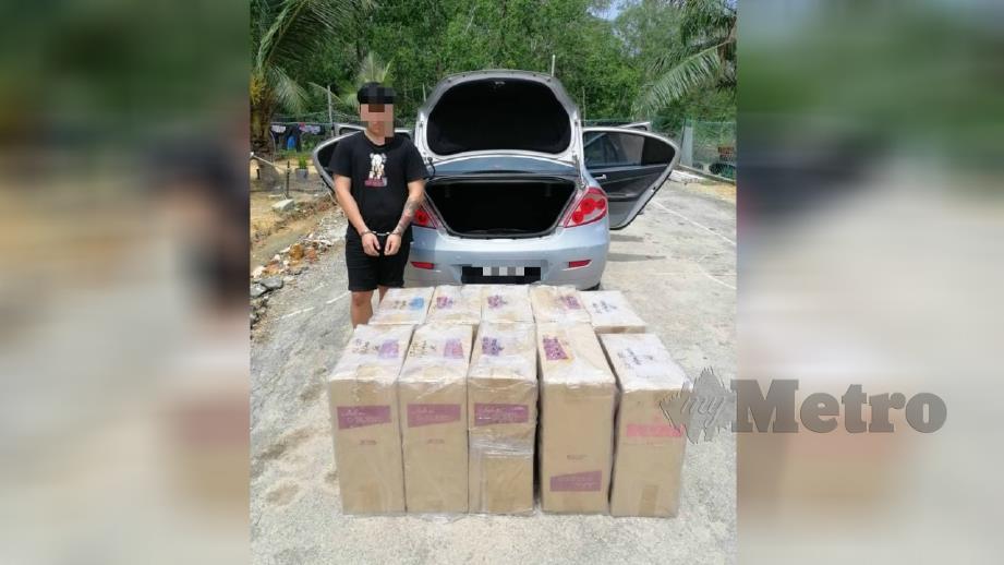 Remaja bersama kotak berisi rokok selepas ditahan anggota PGA di Kampung Sungai Ayam, Batu Pahat hari ini. Foto Ihsan PGA