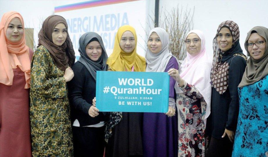 MARLIANA Shamsuddin (tengah) bersama rakan menunjukkan poster kempen World #QuranHour.