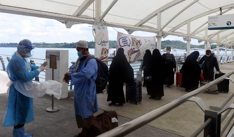 PETUGAS Kementerian Kesihatan Malaysia (KKM) memeriksa suhu badan lapan jemaah tabligh dari Makassar dan Jakarta yang tiba di Terminal Feri Antarabangsa Puteri Harbour sebagai langkah mencegah penularan Covid-19. FOTO BERNAMA