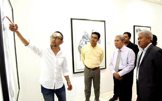 JOHARI (kiri) memberi penerangan kepada tetamu pada perasmian pameran berkenaan.