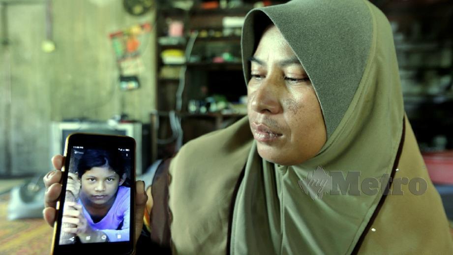 ROHAYA menunjukkan gambar Nor Haslinda yang lemas bersama sepupunya. FOTO Syamsi Suhaimi