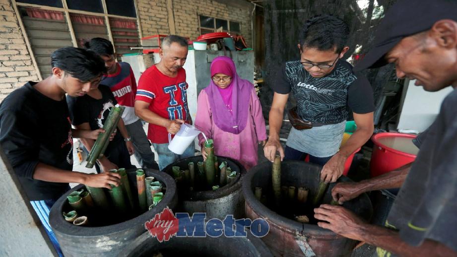 MAZLAN (tiga kanan) melakukan proses membakar lemang di dalam tempayan yang mendapat sambutan di Kampung Sungai Rengas, Kuala Terengganu. FOTO/VIDEO Ghazali Kori