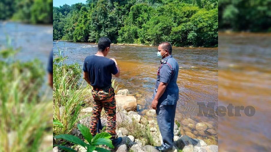 Ketua Zon Machang, Penolong Kanan Penguasa Bomba Mohd Fairus Zakaria (kanan) sedang meninjau lokasi wanita warga emas yang terjatuh di Sungai Kenerong, Kuala Krai petang semalam dan masih belum ditemui. FOTO IHSAN BOMBA