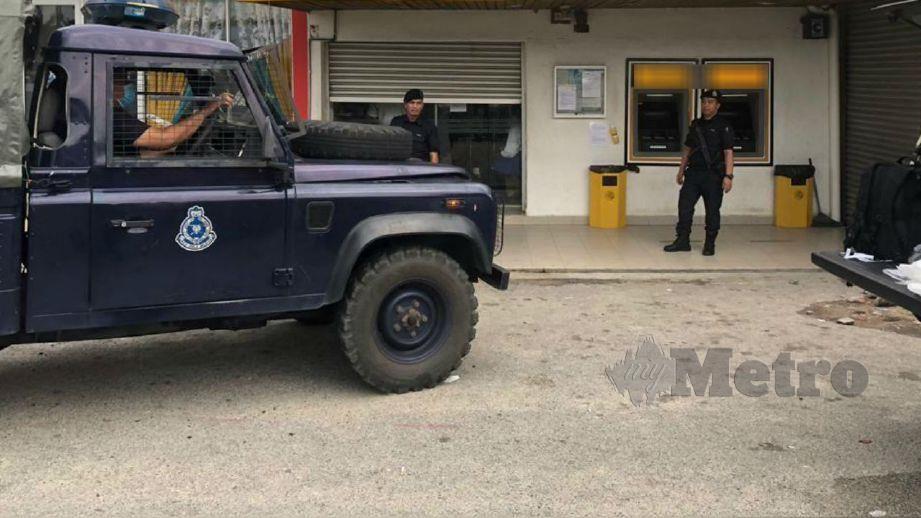 ANGGOTA polis berkawal di luar bank. FOTO ihsan pembaca