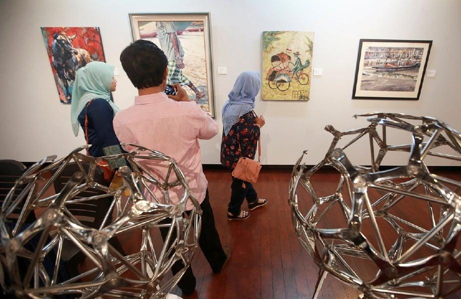 PENGUNJUNG tidak melepaskan peluang melihat pameran seni dua negara. FOTO Sairien Nafis