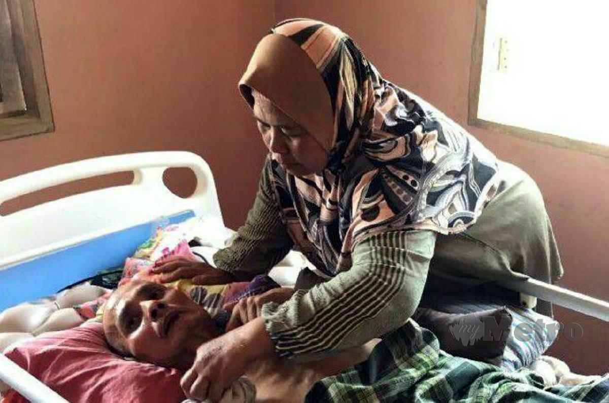 ZAITUN menjaga suaminya yang lumpuh dan tidak boleh bercakap di rumahnya di Kampung Jerek.  FOTO Ramli Ibrahim