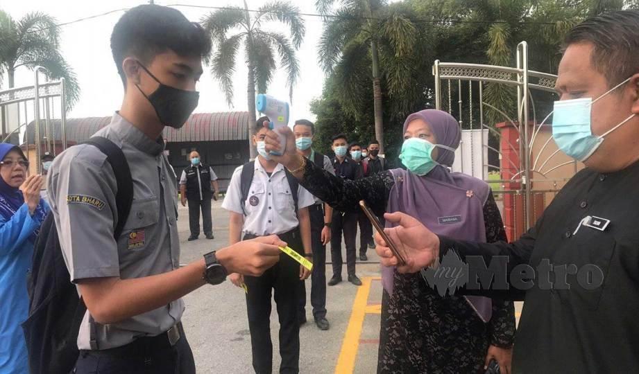 GURU mengambil suhu badan serta mengimbas QR Code untuk merekodkan kehadiran pelajar di SMK Dato Ahmad Maher. FOTO Hazira Ahmad Zaidi
