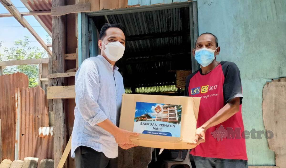 MOHD Azman (kiri) menyerahkan bakul makanan sempena Bantuan Prihatin MAIK kepada Rozili dari Kampung Tandak, Pangkal Meleret. FOTO Siti Rohana Idris