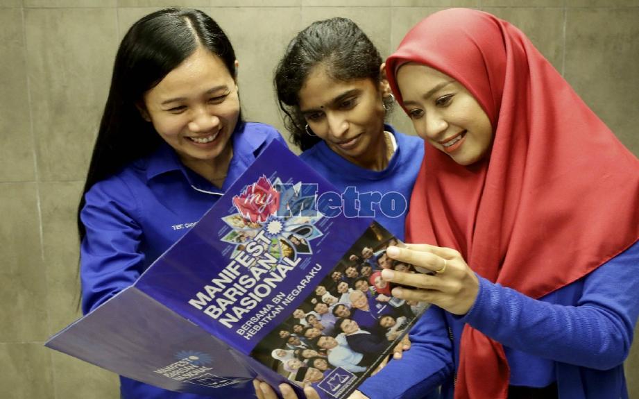 Dari kanan, Fatin Izzaty Muhammad bersama Kumar Nahu dan Tee Choon Ser melihat buku manifesto BN selepas majlis pelancarannya. FOTO Syarafiq Abd Samad