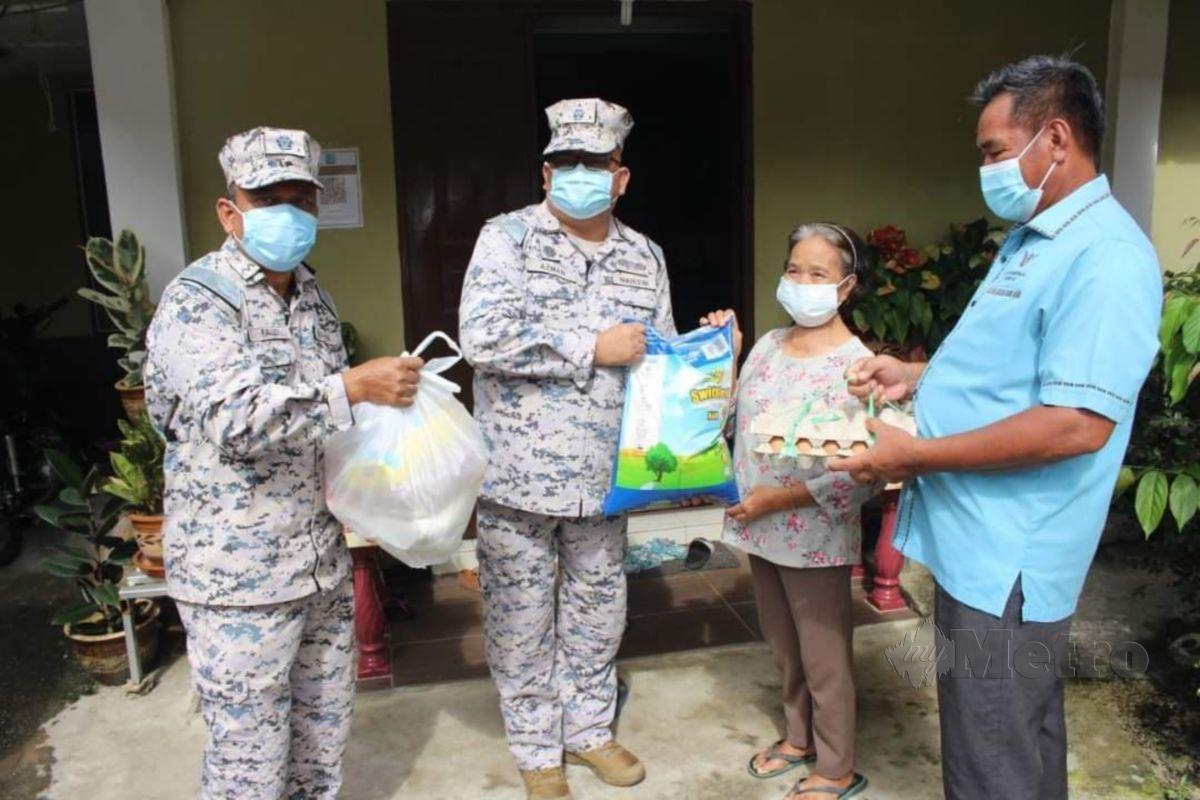 Zin Azman (dua dari kiri) menyampaikan sumbangan bakul makanan kepada komuniti maritim di Kampung Selabat, Bako,Kuching. FOTO NORSYAZWANI NASRI