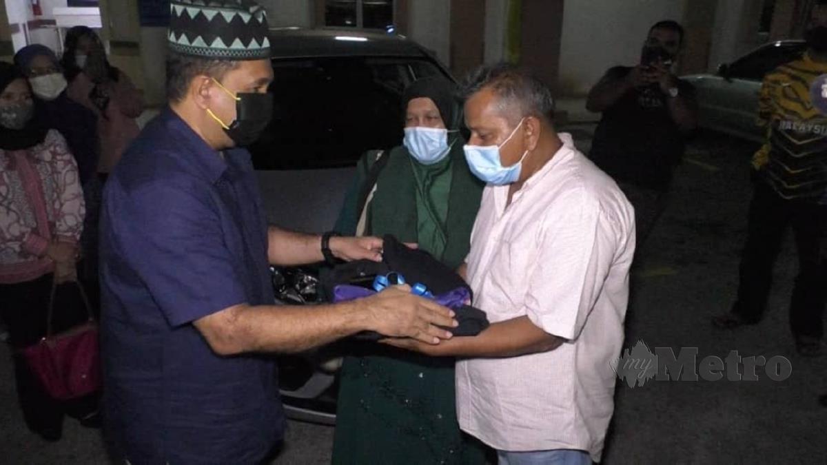 KETUA Polis Pulau Pinang Datuk Sahabudin Abdul Manan menyerahkan pakaian seragam kepada ibu bapa Konstabel Muhammad Iqbal Mazlan sebagai simbolik penghormatan terakhir. FOTO ZUHAINY ZULKIFFLI