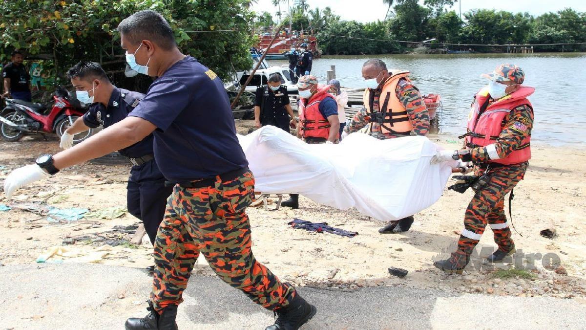 Anggota polis dan bomba mengusung mayat yang dibawa ke Hospital Tumpat bagi proses bedah biasat. Foto Nik Abdullah Nik Omar