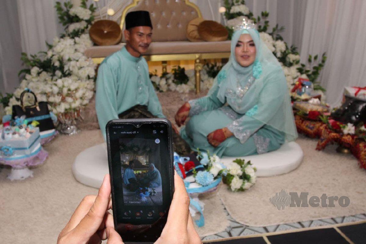 AHLI keluarga menyaksikan majlis perkahwinan pasangan Muhammad Fikri dan Nik Nur Munirah secara atas talian. FOTO Nik Abdullah Nik Omar