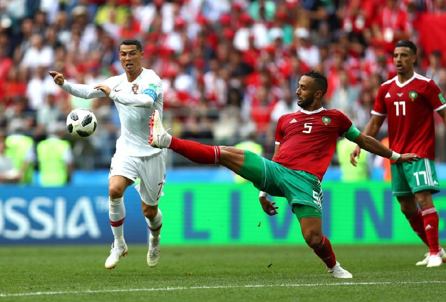 BENATIA (tengah) cuba menghalang penyerang Portugal, Cristiano Ronaldo pada Piala Dunia Russia 2018. — FOTO Getty Images