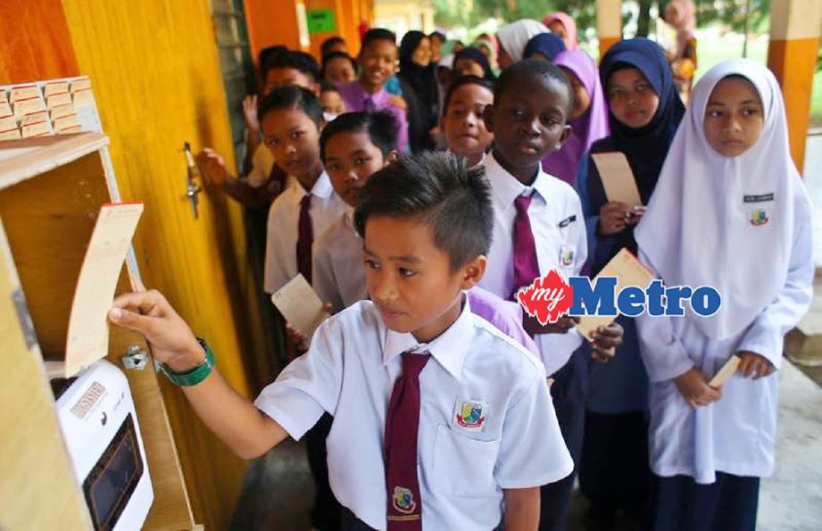 Murid SK Kompleks Gong Badak, Kuala Nerus, menggunakan mesin perakam waktu kedatangan bermula hari ini. - Foto GHAZALI KORI