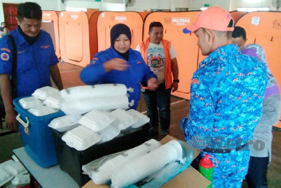 ANGGOTA APM mengagihkan makanan kepada mangsa banjir. FOTO ihsan APM
