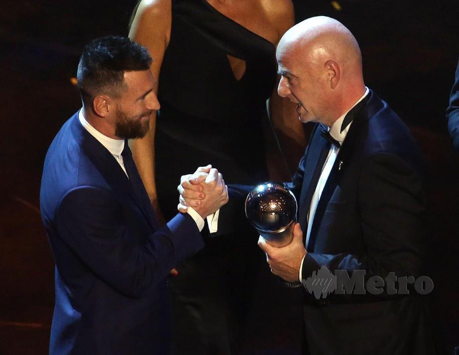MESSI (kiri) menerima trofi daripada Presiden FIFA, Gianni Infantino. — FOTO EPA