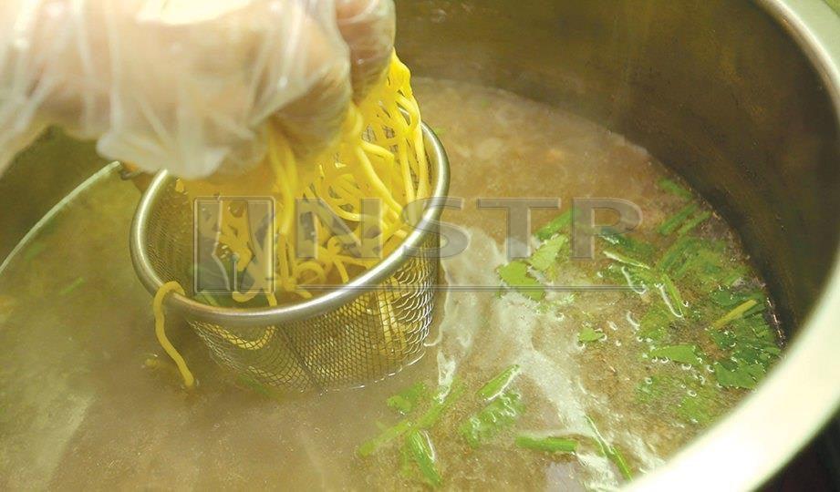 5. CELUR mi kuning di dalam kuah sup yang sedang mendidih.