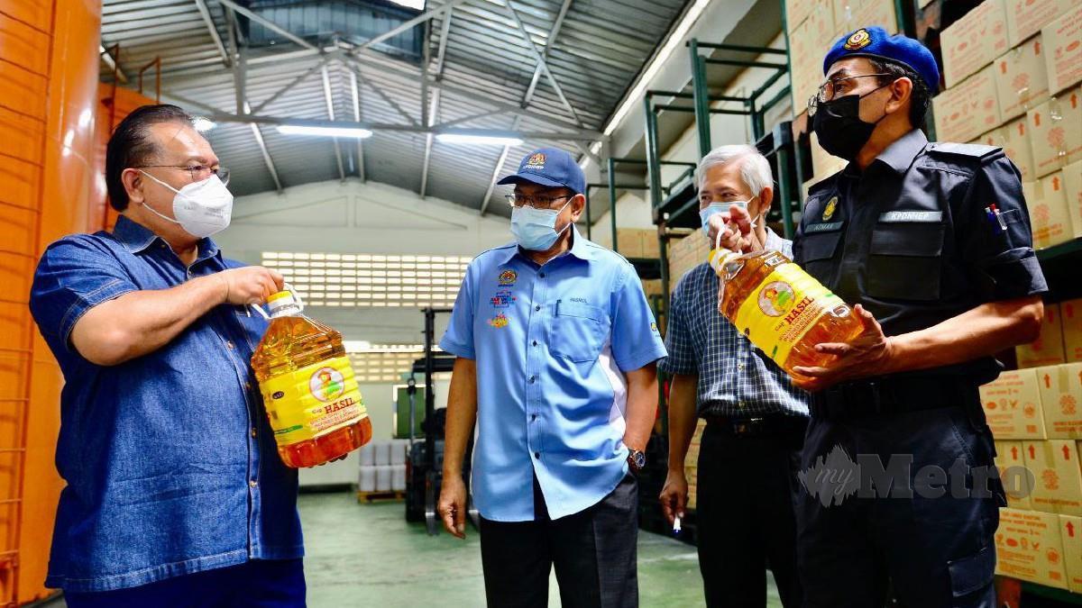 Alexander (kiri) ketika mengadakan lawatan kerja ke sebuah pusat pengeluaran minyak masak. Foto Ihsan KPDNHEP