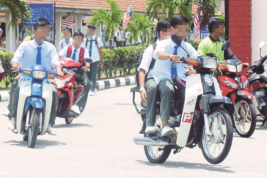 RAMAI pelajar tidak memakai topi keledar ketika menunggang motosikal.