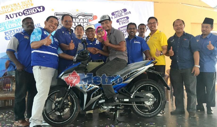 MOHD Fadzil duduk di atas motosikal dimenanginya pada Program Cabaran Servis 1,000 Motosikal di Arena Square Batu Gajah, Batu Gajah, hari ini. FOTO Razif Rosli