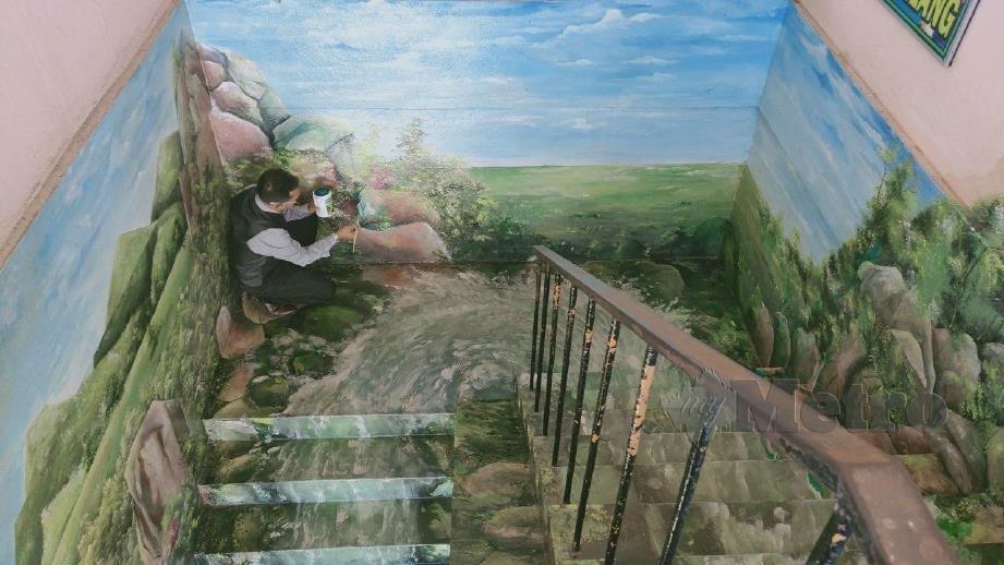 RUSLAN menyiapkan lukisan mural pada tangga di SK Pida 3, Tunjang. FOTO Zuliaty Zulkifli.