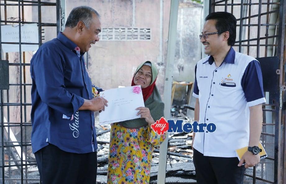 Mohamed Hasnan (kiri) menyampaikan surat tawaran pembinaan RMR1M kepada Asnah Mustafa, 64, di tapak rumahnya yang musnah dalam kebakaran di Kampung Baru, Wakaf Che Yeh. - Foto FATHIL ASRI