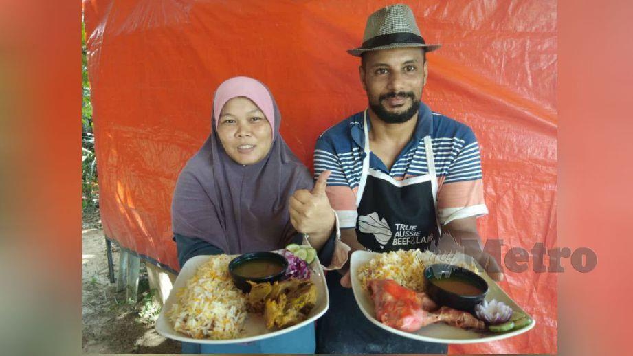SALAHELDIN Mahmoud bersama Hira menunjukkan nasi Arab yang dijual di gerai mereka di Kampung Sungai Hala. FOTO Syaherah Mustafa