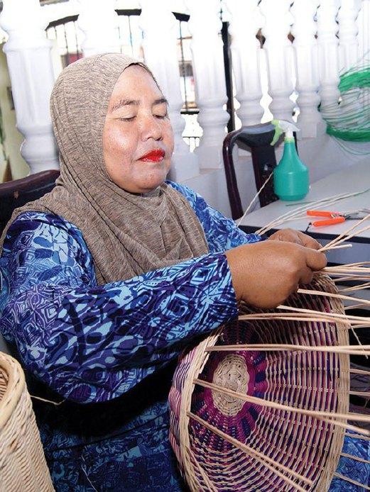 AZIZAH tekun menyiapkan produk kraf di kediamannya.
