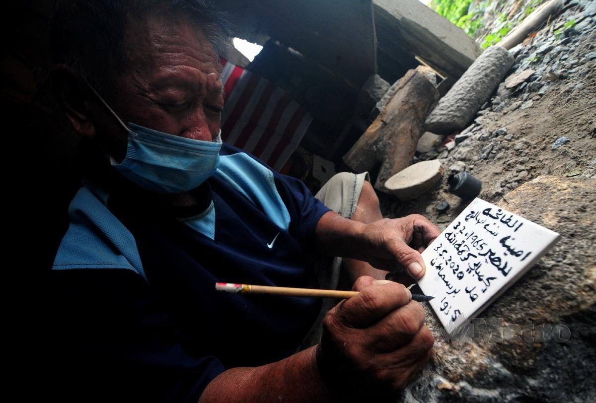 Kuah Leong Chuan, menulis nama dengan tulisan Jawi di atas batu nisan. FOTO BERNAMA