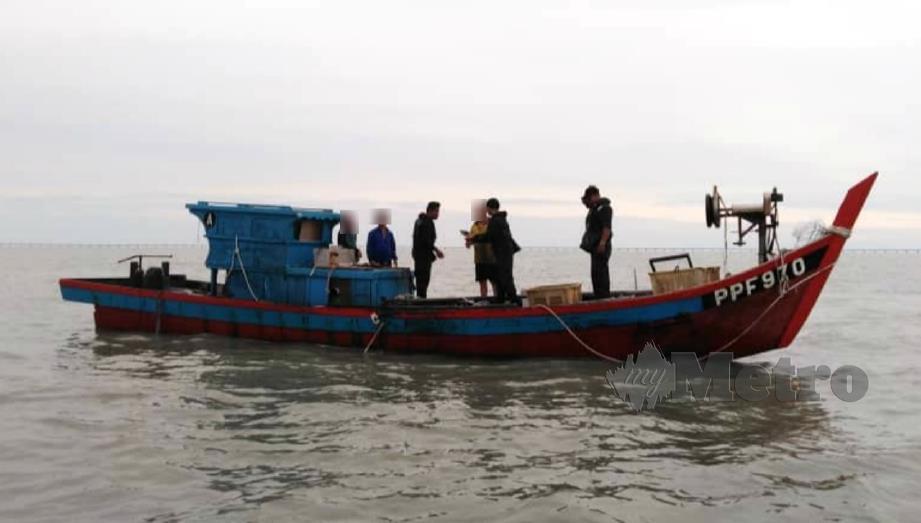ANGGOTA APMM menyiasat bot nelayan yang menggunakan peralatan tidak dilesenkan. FOTO Ihsan APMM.