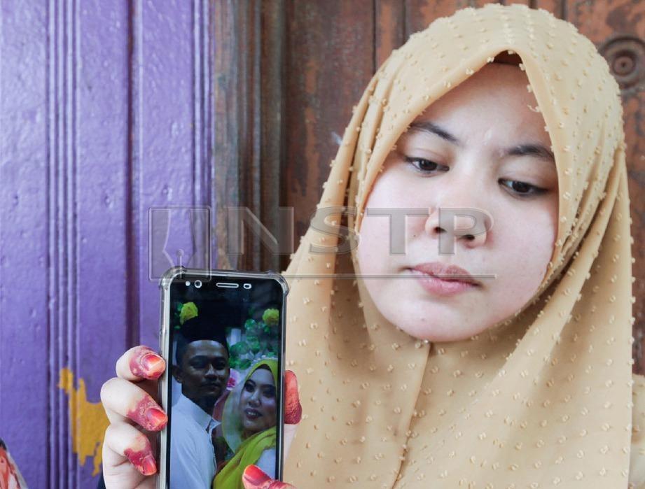 Nor Shahirah Mohd Fuad, menunjukkan gambar perkahwinan bersama arwah suaminya. FOTO Syamsi SUHAIMI