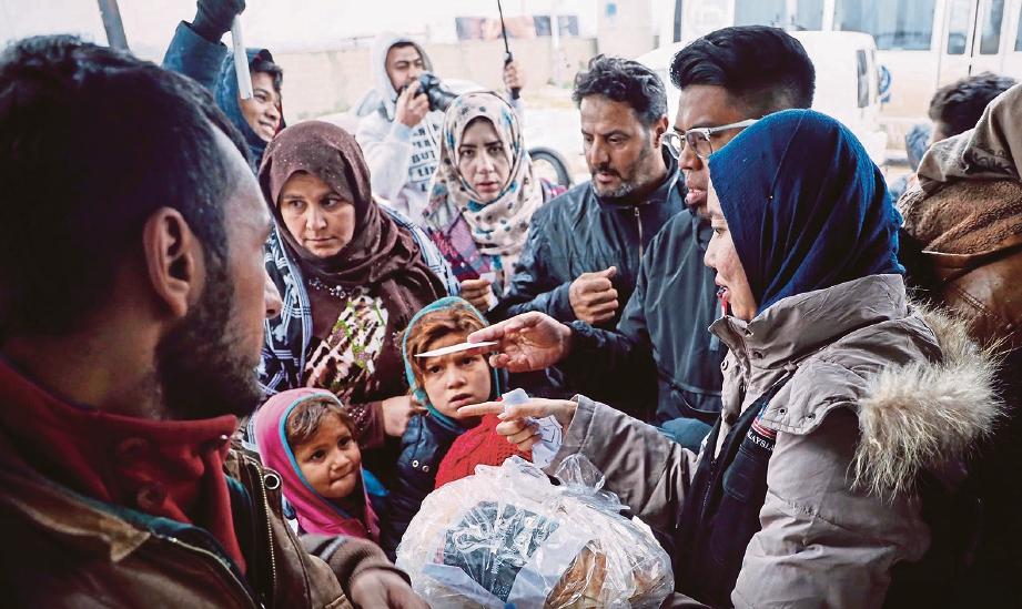 PUTERI Norafiah membantu mengagihkan makanan kepada pelarian, Misi Musim Sejuk 7.0 Persatuan Cinta Syria Malaysia (CSM).
