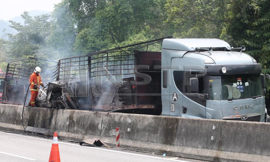 ANGGOTA bomba memadam kebakaran treler dan kereta yang terbabit kemalangan di Kilometer 255.6 Lebuhraya Utara Selatan arah utara selepas Terowong Menora, kelmarin. FOTO L Manimaran