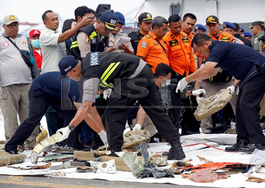 ANGGOTA penyelamat menyusun serpihan pesawat Lion Air di pelabuhan Tanjung Priok, Jakarta. FOTO Reuters