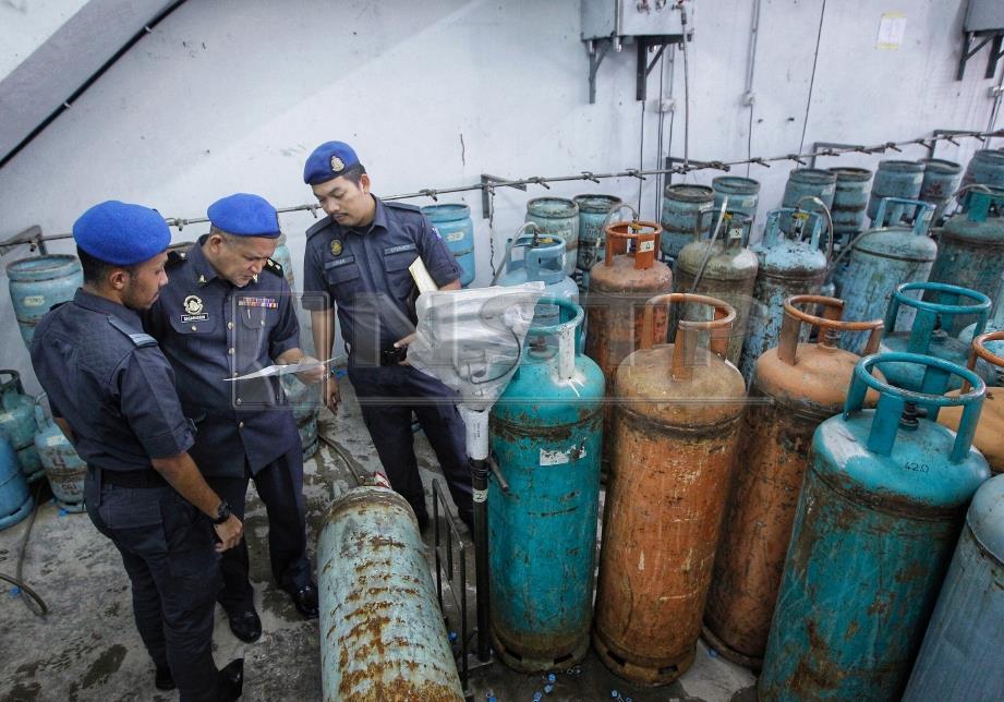 BASARUDDIN memeriksa tong LPG yang dirampas dalam operasi membanteras penyelewengan barang kawalan di Jalan Teruntum 12, Meru, Klang. FOTO Saddam Yusoff