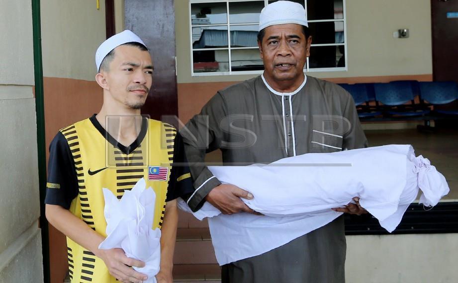MEOR Ikram (kiri) membawa pulang jenazah anaknya. FOTO Abdullah Yusof